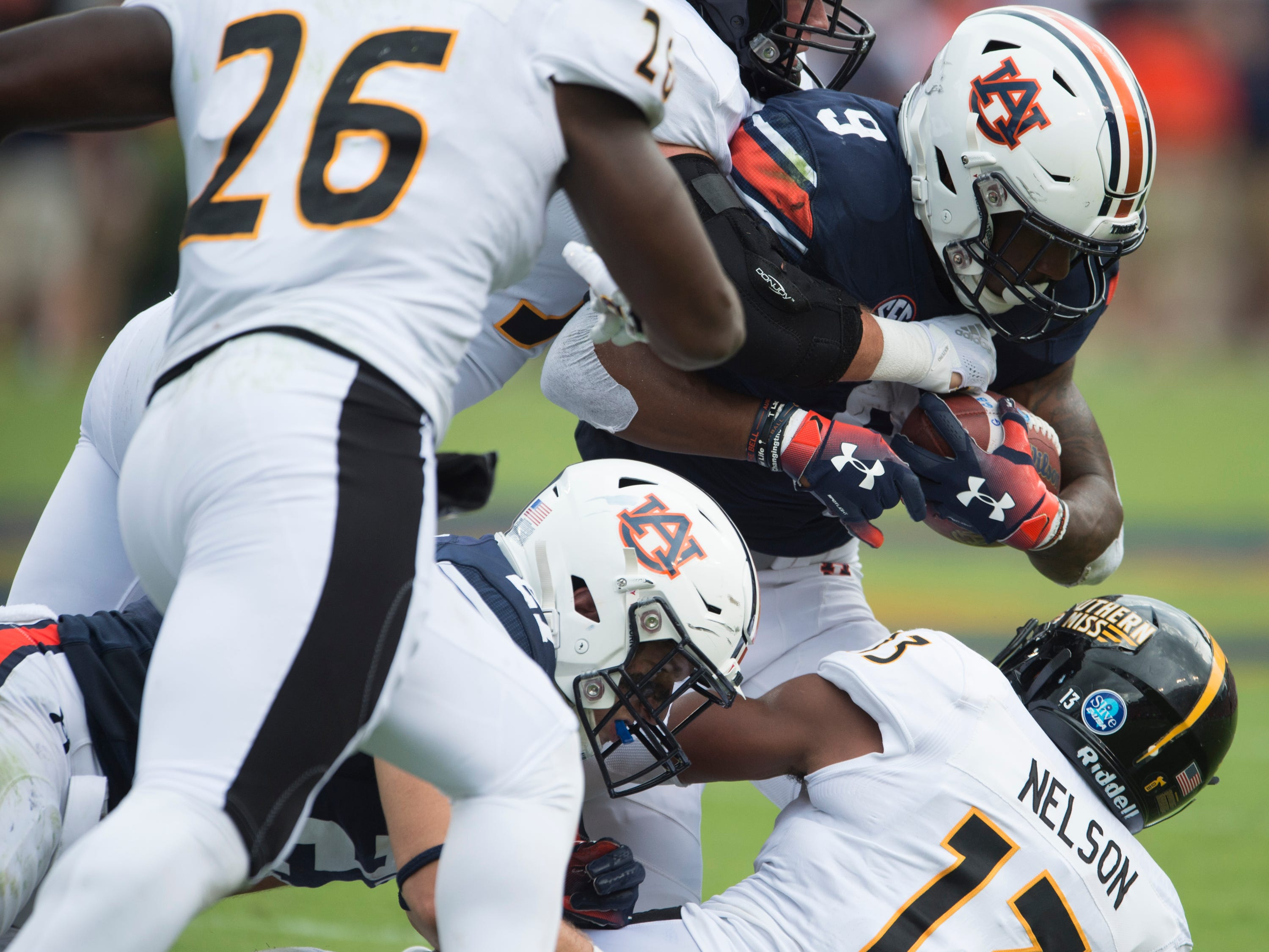 Auburn's Kam Martin (9) is taken down by a swarm of Southern Miss defenders at Jordan-Hare Stadium in Auburn, Ala., on Saturday, Sept. 29, 2018. Auburn leads Southern Miss 14-3, the game went into a weather delay with 4:27 left in the second quarter.