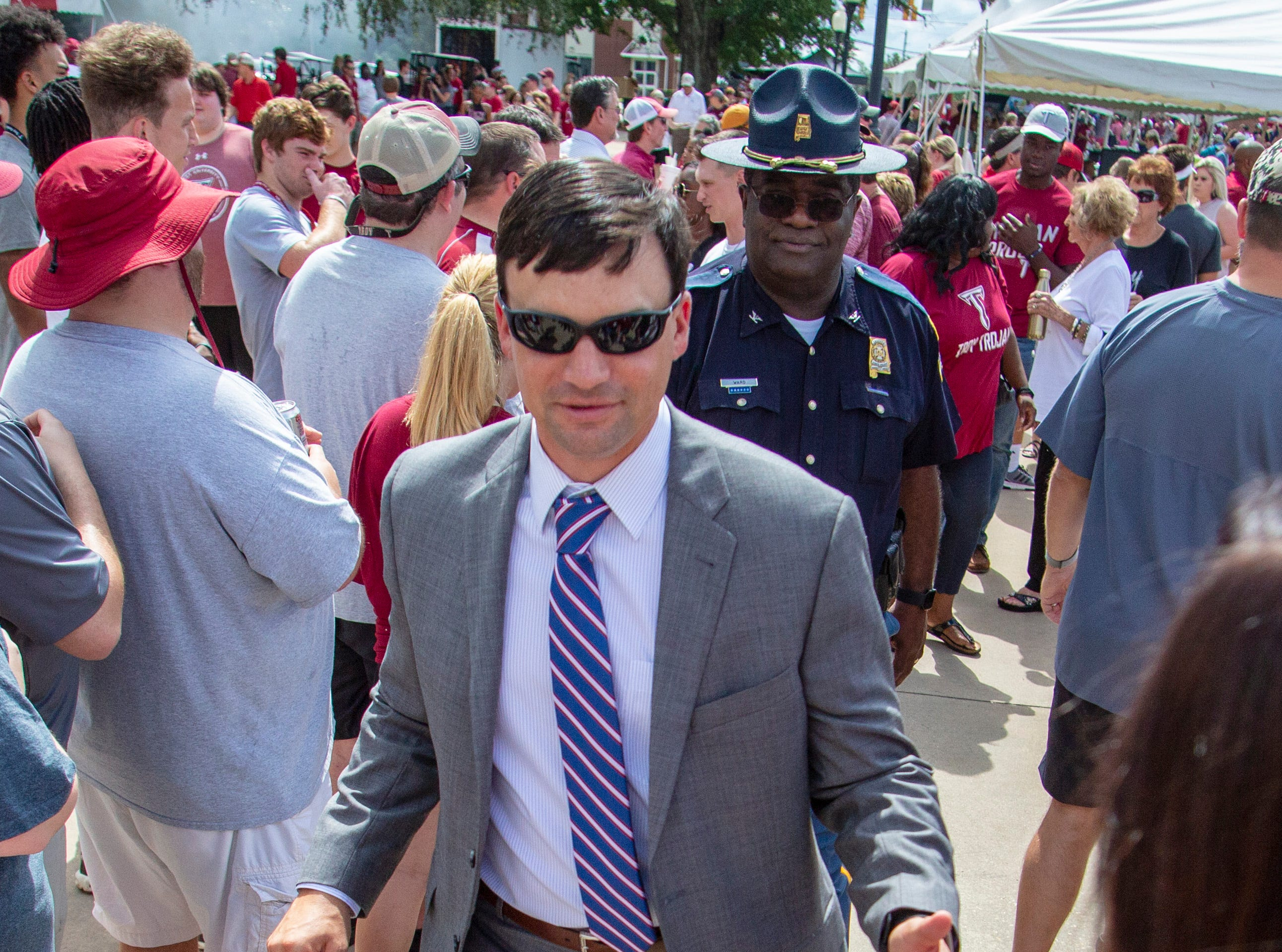 Troy head coach Neal Brown slaps hands with fans as the team is welcomed to the stadium.
