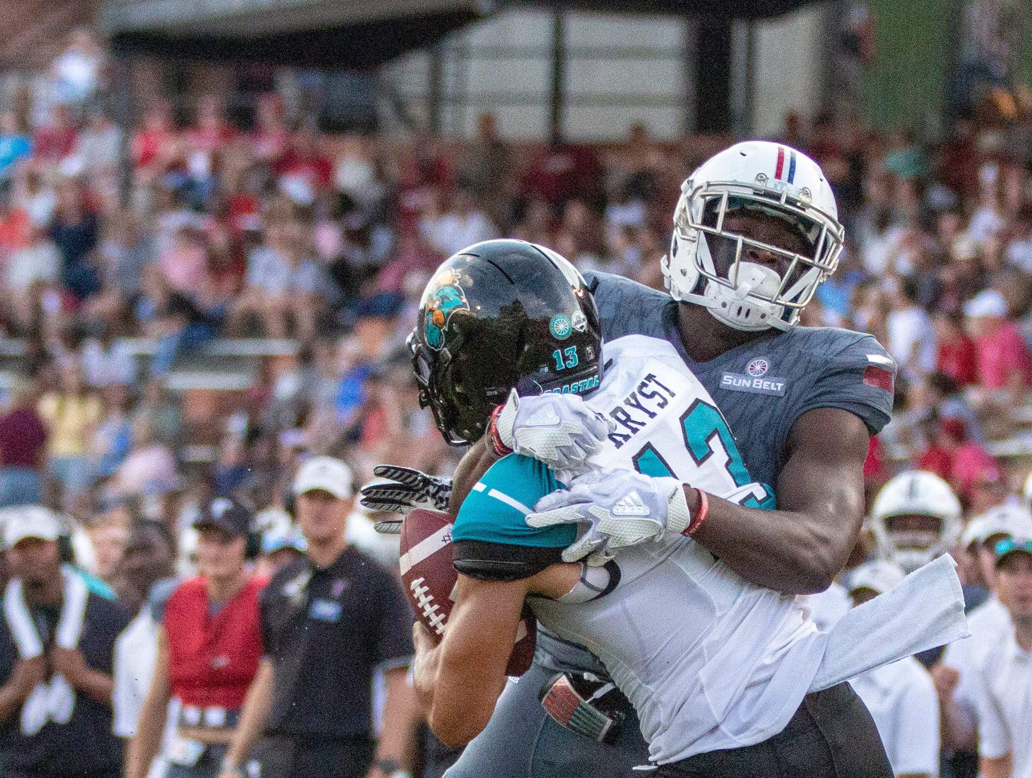 Troy's Demontrez Brown grabs Coastal Carolina's Chandler Kryst after he intercepts the ball late in the fourth quarter.