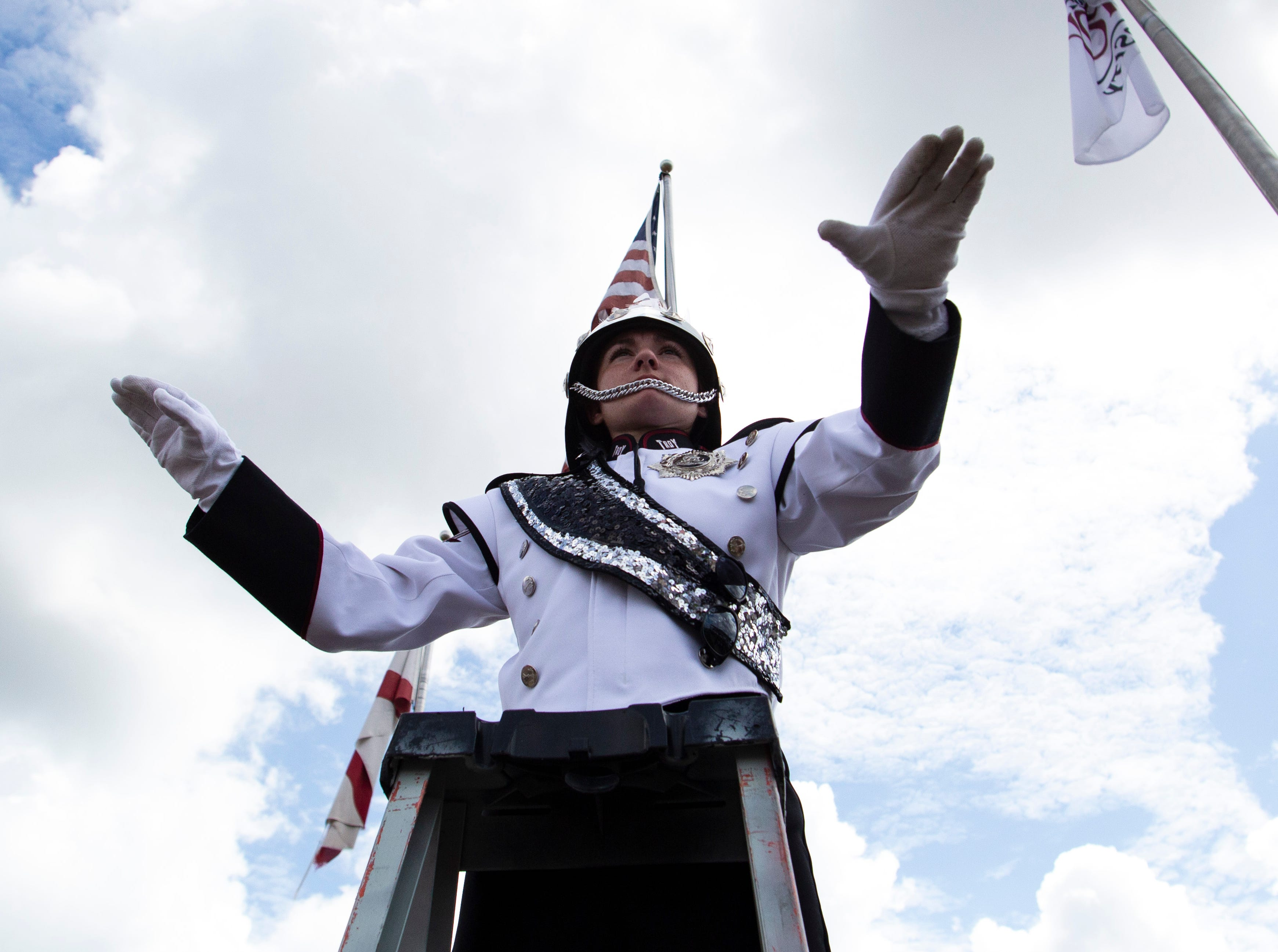 A Troy drum major conducts the band from high during Trojan Walk.