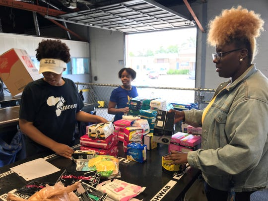 Taylor Owens (right) and other members of Tennessee State University's Sigma Gamma Rho Alpha Beta chapter count Period Project donations on Saturday.