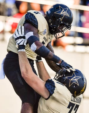 Vanderbilt offensive lineman Devin Cochran (77) holds up running back Ke'Shawn Vaughn (5) after Vaughn scored a touchdown against TSU during the second half at Vanderbilt Stadium in Nashville, Tenn., Saturday, Sept. 29, 2018.