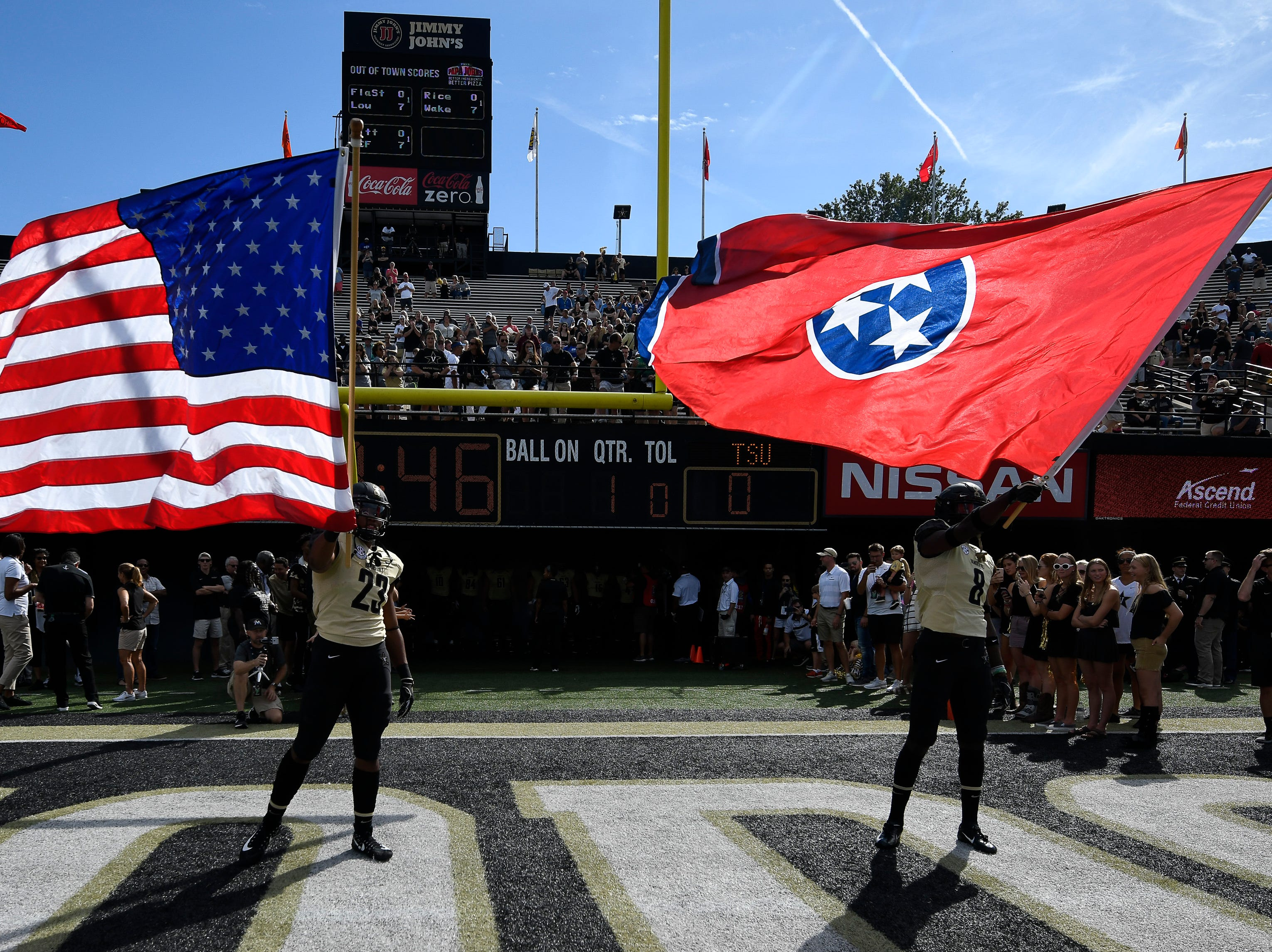 Vanderbilt running back Khari Blasingame (23) and cornerback Joejuan Williams (8) wave the flags before they take the field for their game against TSU at Vanderbilt Stadium Saturday, Sept. 29, 2018, in Nashville, Tenn.