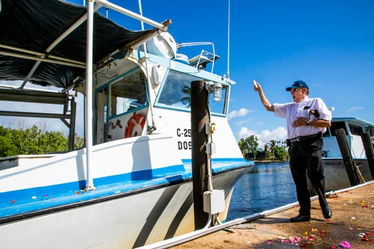 The Rev. Tim Navin throws holy water on the Kristin Anne during the Blessing of the Stone Crab Fleet at the Rod & Gun Club in Everglades City on Saturday, Sept. 29, 2018. The Blessing of the Fleet is a tradition that began centuries ago in Mediterranean fishing communities and is meant to ensure a safe and bountiful season.