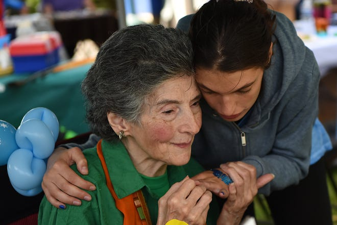 """Rosemarie D'Alessandro is comforted by Sophia Rowe during Joan's Joy Foundation's 4th annual """"Child Safety Fest"""" at the Joan Angela D'Alessandro White Butterfly Sculpture and Garden in Hillsdale on Saturday September 29, 2018."""