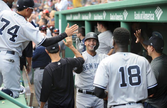 New York Yankees second baseman Gleyber Torres (25) is greeted in the dugout after hitting a two run home run during the fourth inning against the Boston Red Sox at Fenway Park.