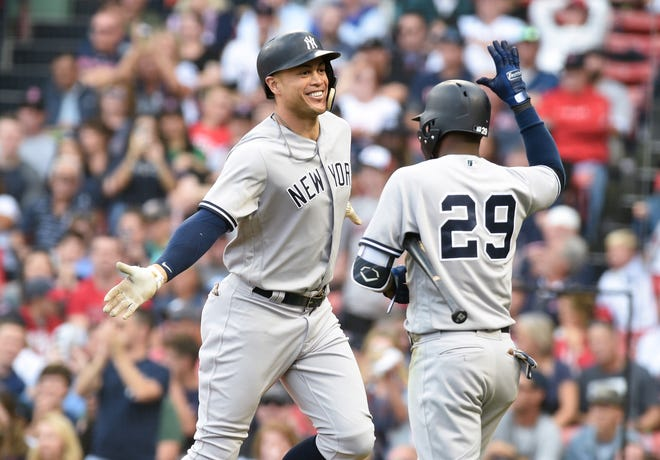 New York Yankees designated hitter Giancarlo Stanton (27) reacts with shortstop Adeiny Hechavarria (29) after hitting a home run during the seventh inning against the Boston Red Sox at Fenway Park.