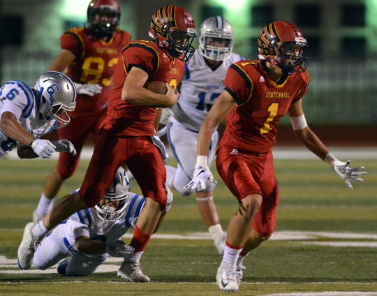 Centennial's Aiden Trujillo (1) leads the way for quarterback Lance Frost against Carlsbad on Friday night at Field of Dreams.