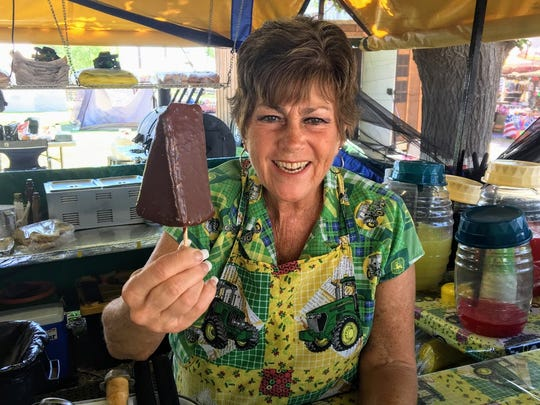 Sonya Siefkes, co-owner of Fun-tastic Concessions food stand, holds up a chocolate dipped cheesecake at the Southern New Mexico State Fair & Rodeo on Saturday, Sept. 29, 2018.