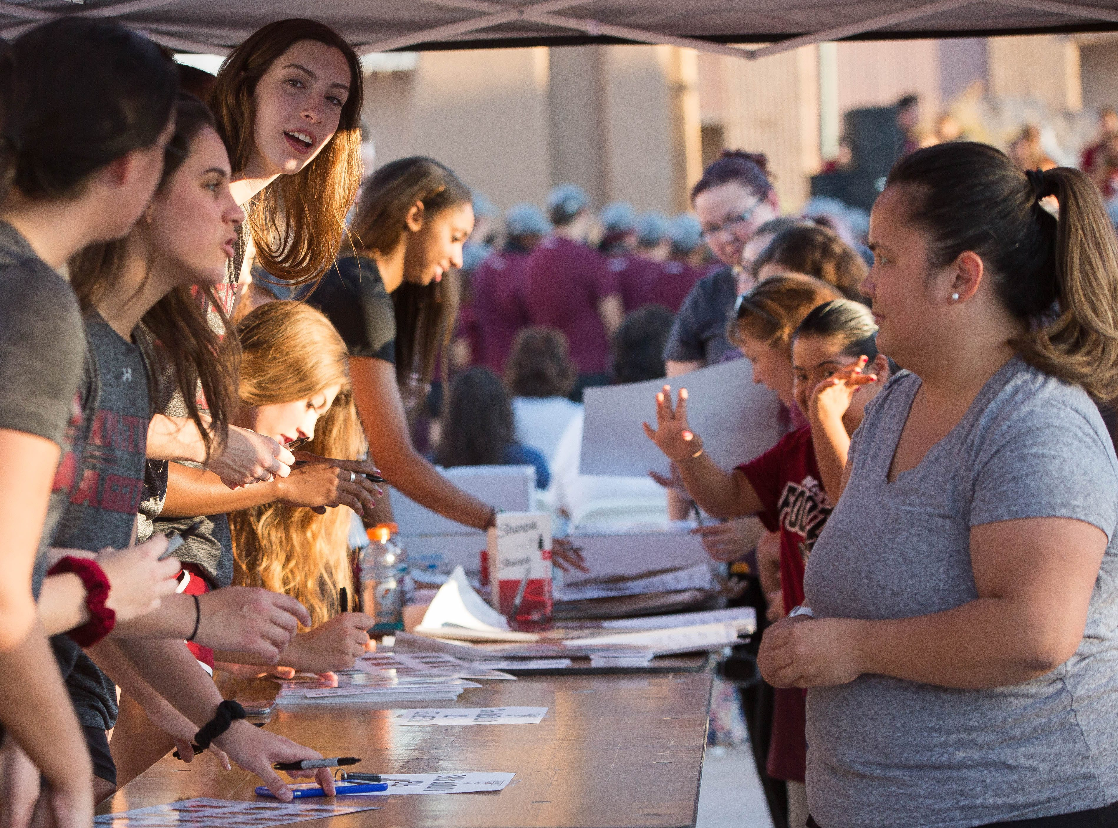 The New Mexico State University Volleyball team signs autographs at the Downtown Aggie Rally, Friday September 28, 2018.