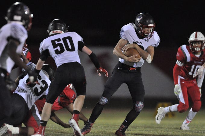 NMMI Colt quarterback tries to hold on to the ball Sept. 28 against the Loving Falcons.