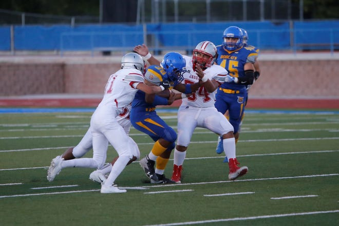 Bloomfield's Kenyon Mosley fights for extra yards on the opening kick return before being tackled by Valencia's Brandon Guillen (54) during Friday's game at Bobcat Stadium.