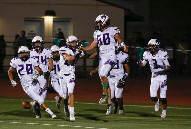 Kirtland Central's Cadyn Hartsfield (58) celebrates after scoring a touchdown against Farmington during Friday's game at Hutchison Stadium in Farmington.
