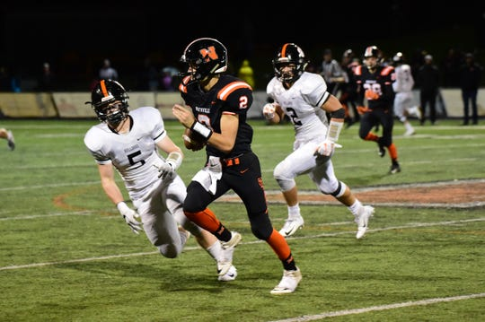 Scampering out of trouble is Northville quarterback Trevor Schornack (2). Brighton players Cole Riddle (5) and Zach Pardonnet (2) close in.