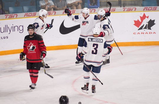 Jack Hughes (19) congratulates older brother Quinn Hughes after scoring a tournament goal for Team USA against Canada.