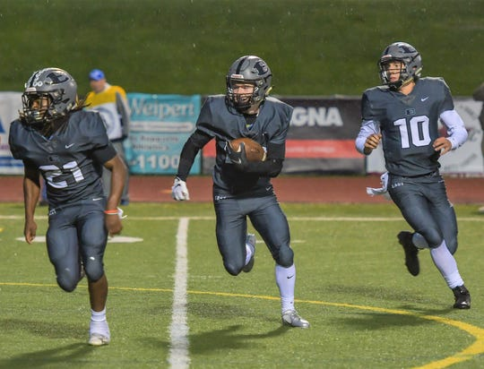 South Lyon East's Matt Gilbert (middle) takes the handoff from quarterback Chris Kaminski (1) as Terry Day takes the lead block.