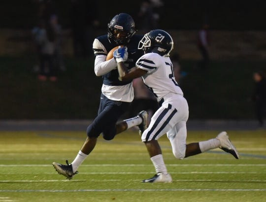 Loyola defender Marquise Henderson (21) puts the clamps on Cranbrook receiver Kobi Russell during Friday's Catholic League AA Division battle.