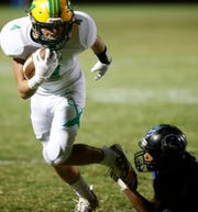 Coachella Valley High School's Angelo Fitzgerald runs for yards against Cathedral City High School.