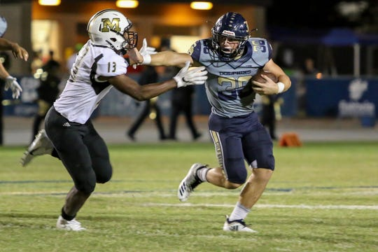 Gulf Breeze's Tyler Dittmer (36) stiff arms and gets away from Milton's Kameryn Hall (13) in the District 2-6A game at Gulf Breeze High School on Friday, September 28, 2018.