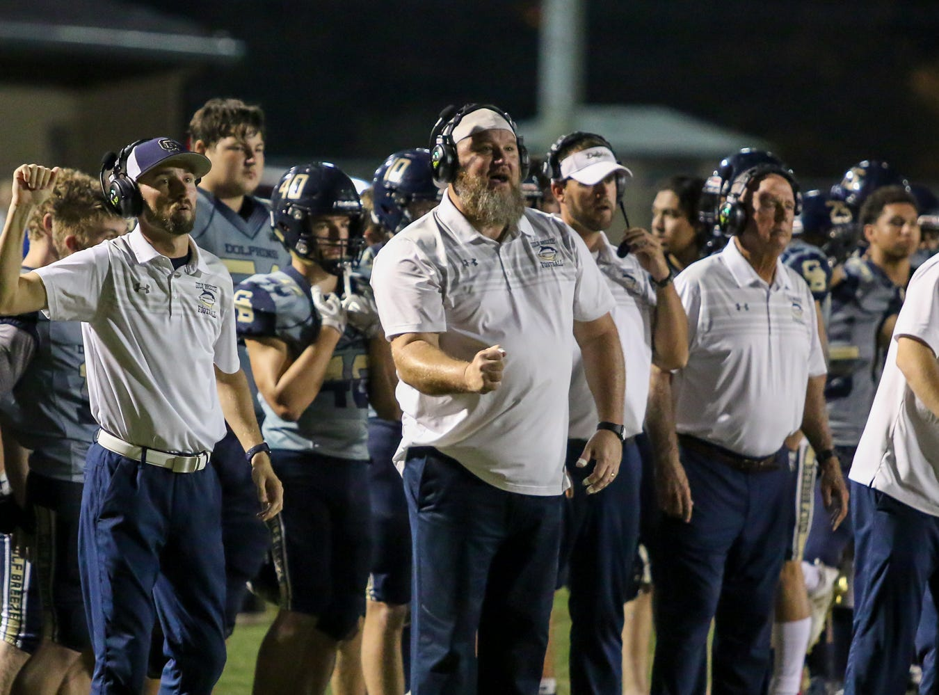 Gulf Breeze coaches call in a defensive goal line play against Milton in the District 2-6A game at Gulf Breeze High School on Friday.