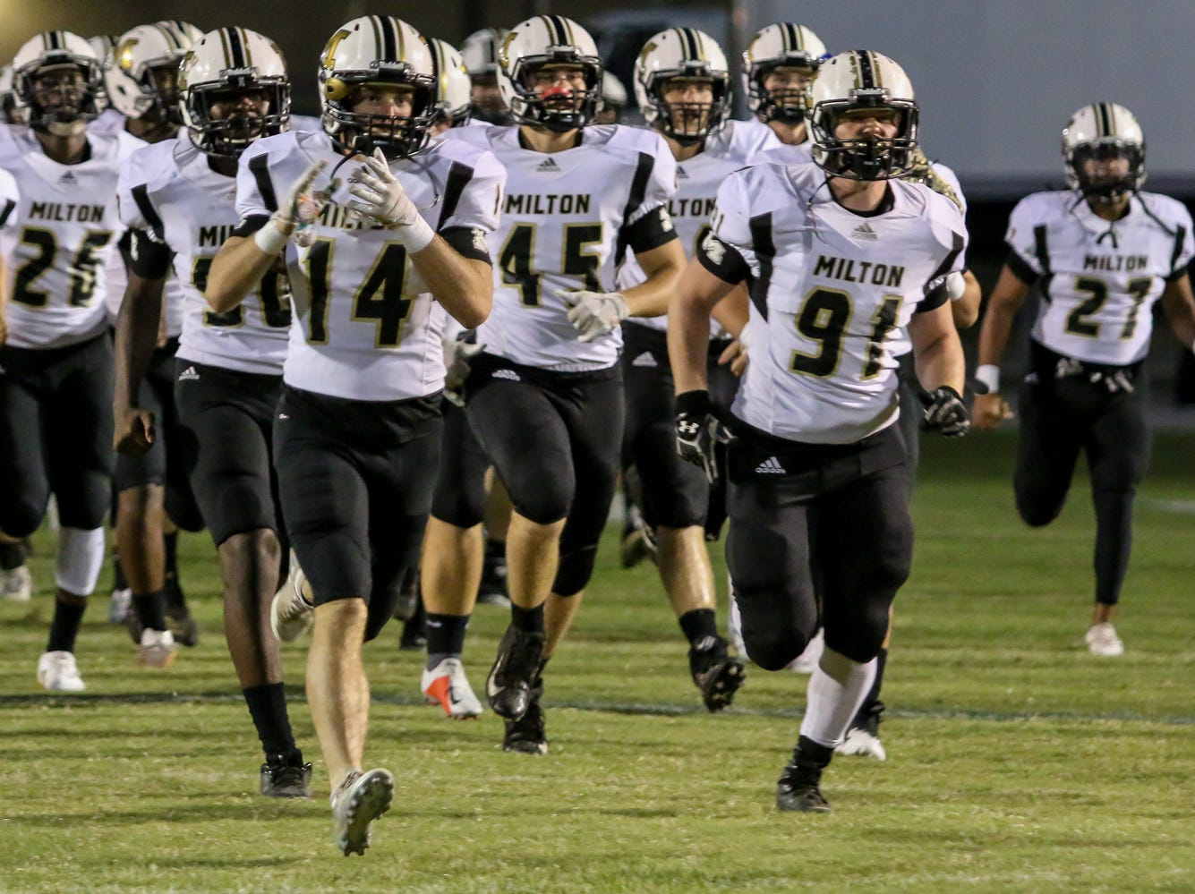 The Milton Panthers take the field against Gulf Breeze before the District 2-6A game at Gulf Breeze High School on Friday, September 28, 2018.