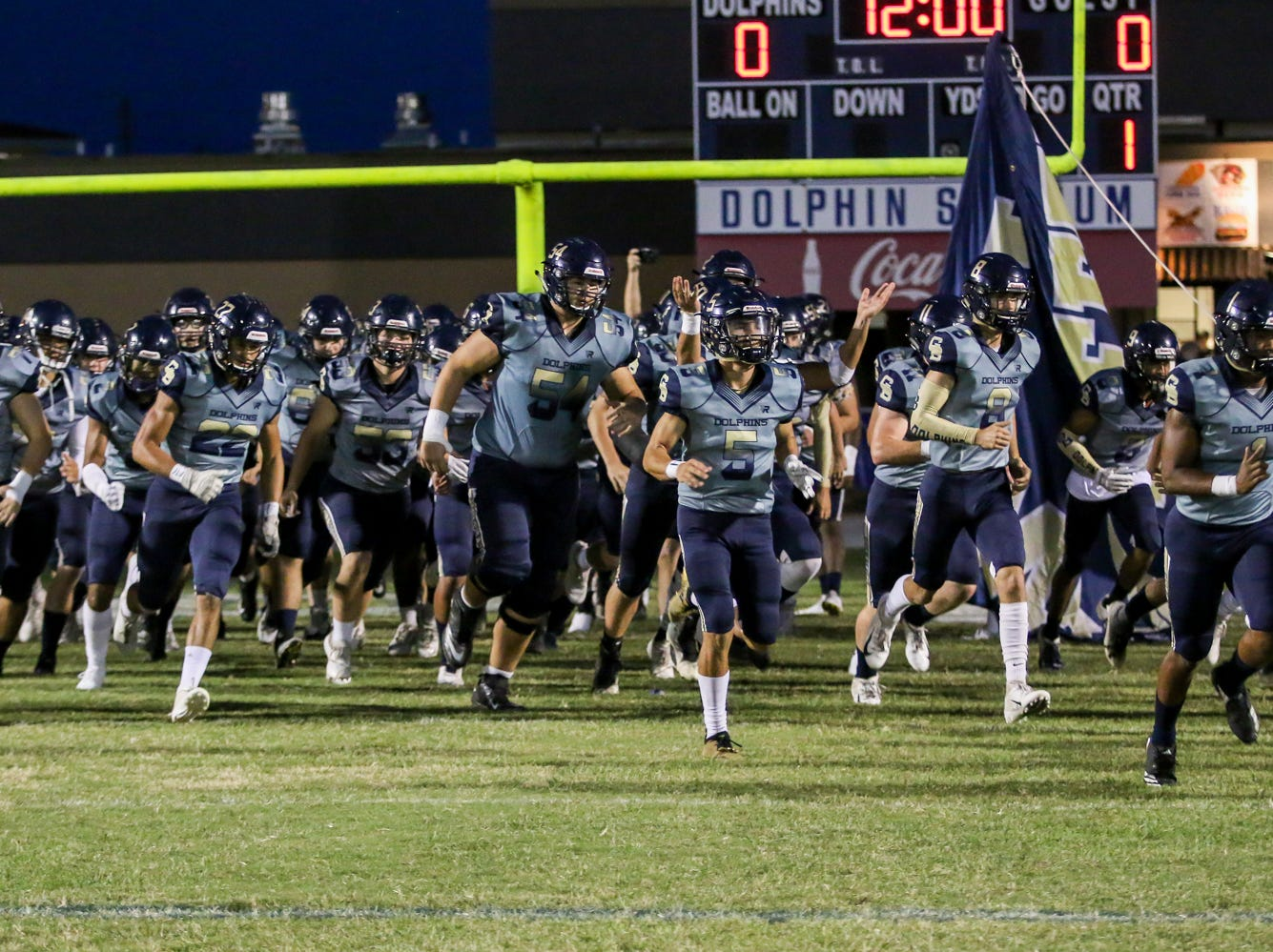 The Gulf Breeze Dolphins take the field against the Milton Panthers before the District 2-6A game at Gulf Breeze High School on Friday.