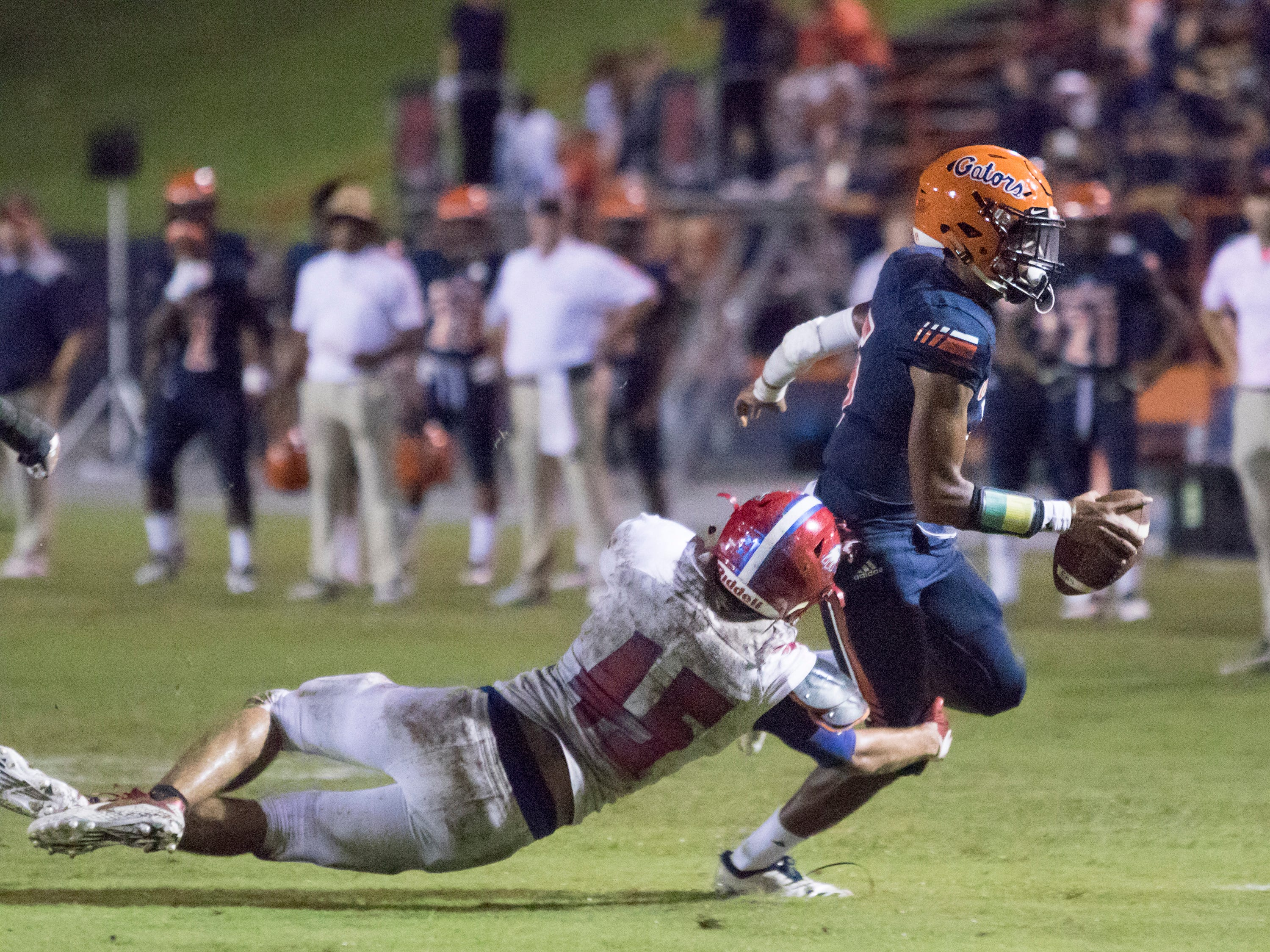 Quarterback Av Smith (5) slips the tackle of Wyatt Gill (45) during the Pine Forest vs Escambia football game at Escambia High School in Pensacola on Friday, September 28, 2018.