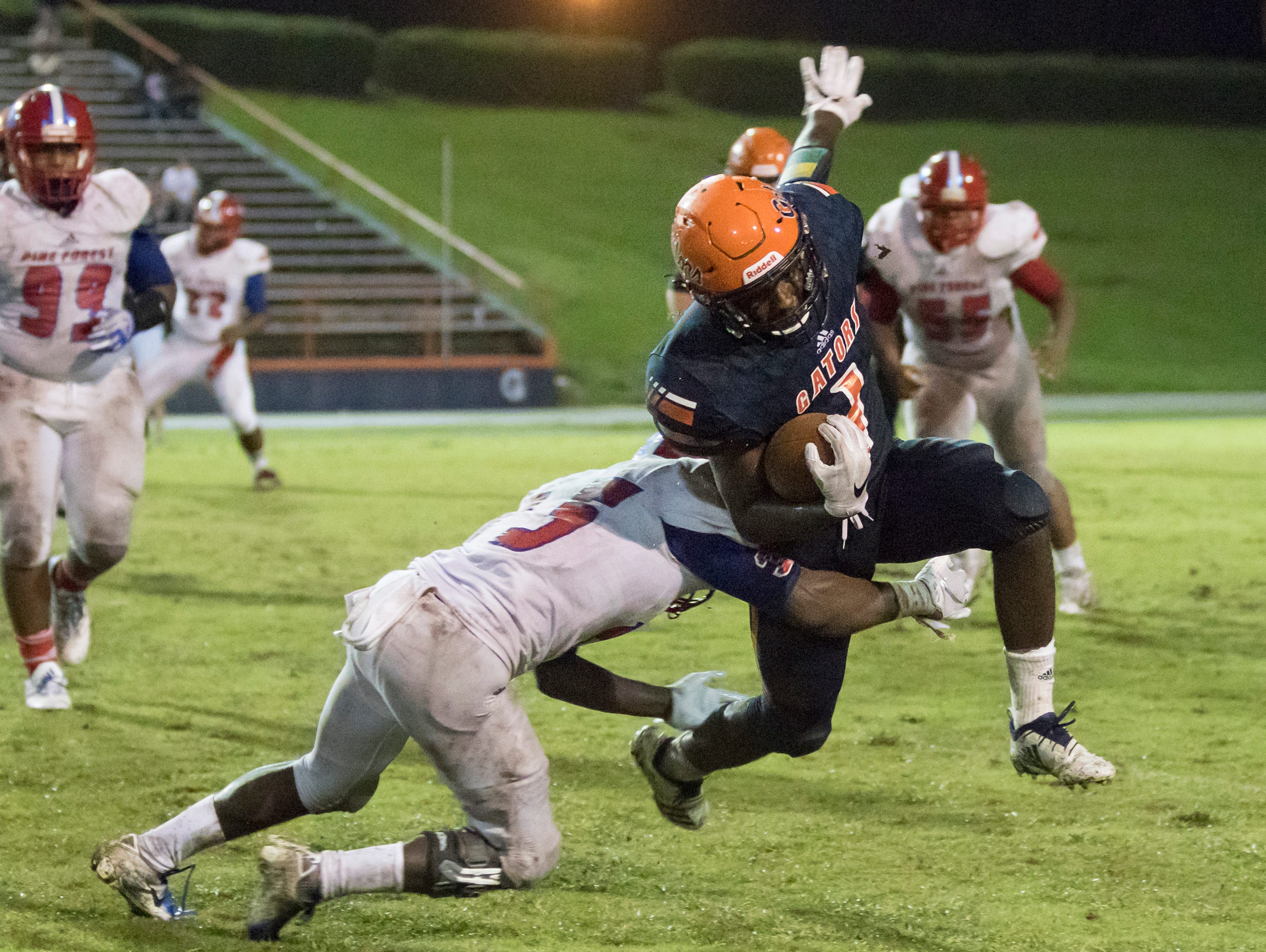 Mitrez Rawls (15) brings down Frank Peasent (1) during the Pine Forest vs Escambia football game at Escambia High School in Pensacola on Friday, September 28, 2018.