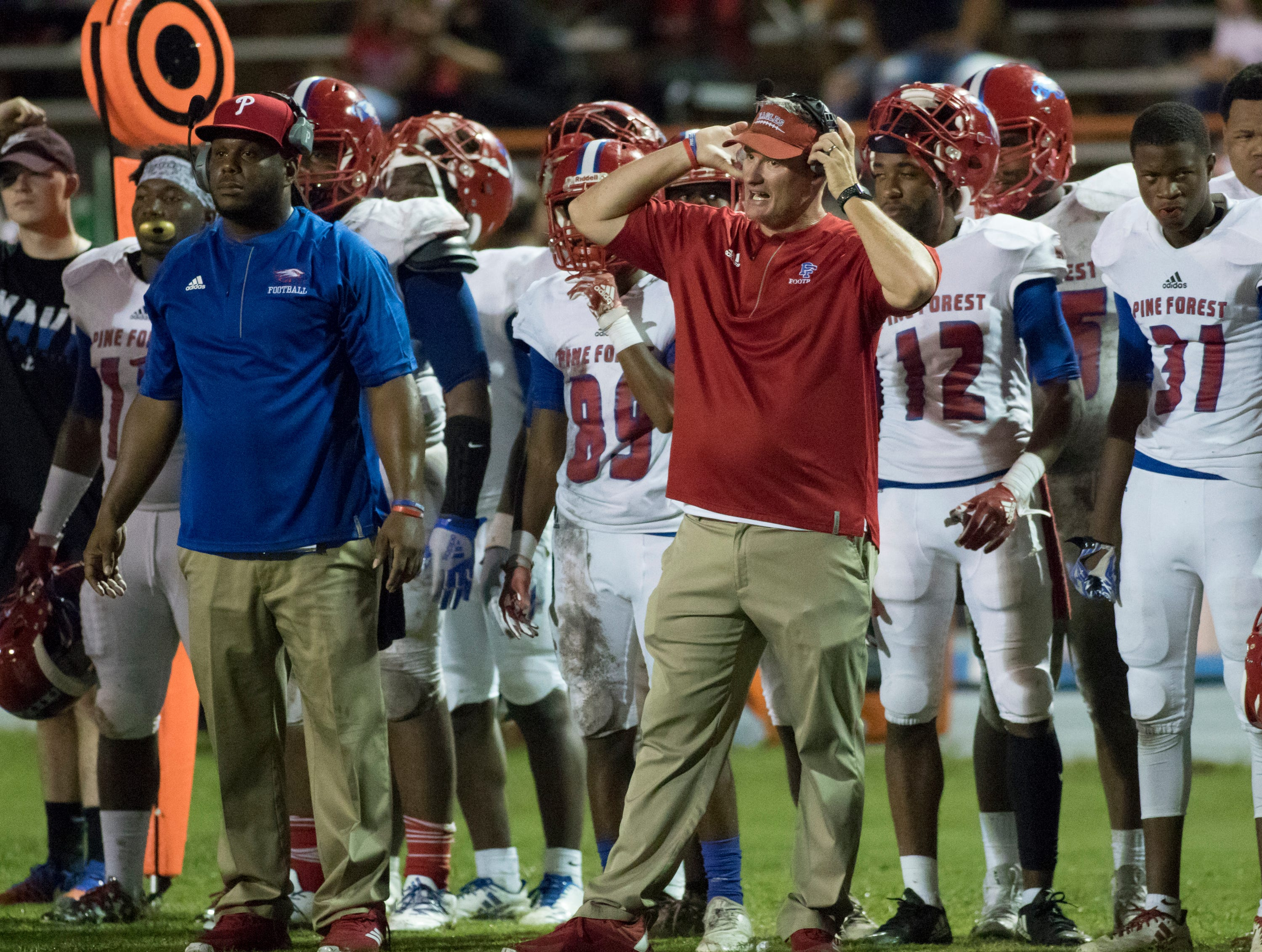 Eagles head coach Jason McDonald (in red shirt) communicates with his coaches during the Pine Forest vs Escambia football game at Escambia High School in Pensacola on Friday, September 28, 2018.
