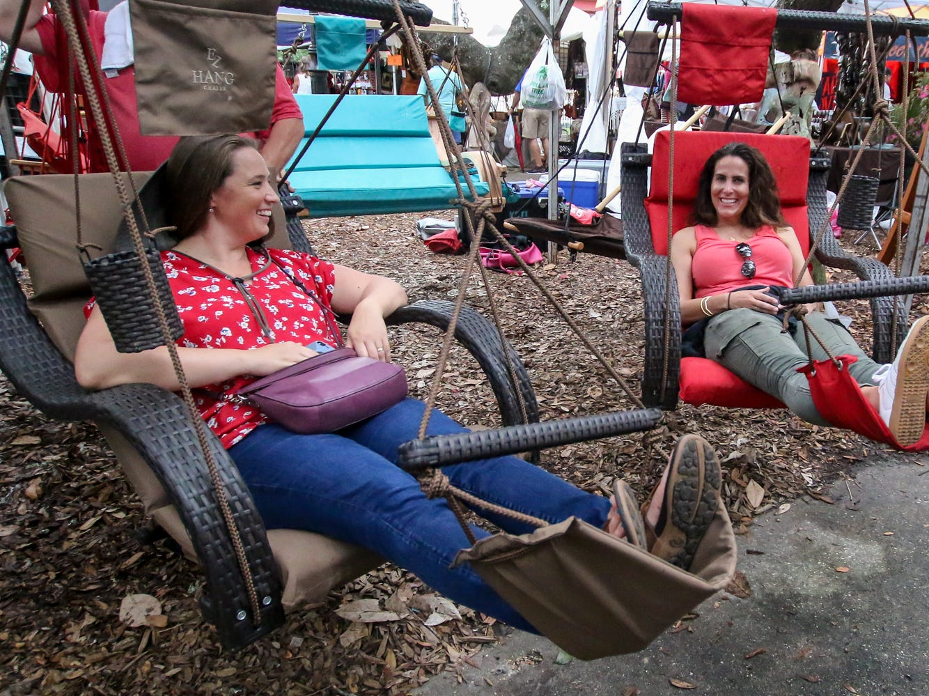 Mary Henry, of Yorktown, Va., left, and Michele Bennett, of Farmington, Utah, relax in a couple of swings during the first day of the 41st annual Pensacola Seafood Festival in downtown Pensacola on Friday, September 28, 2018. The festival, which features multiple food vendors, artists, cooking demonstrations, live music and more, is free to enter and continues through Sunday.