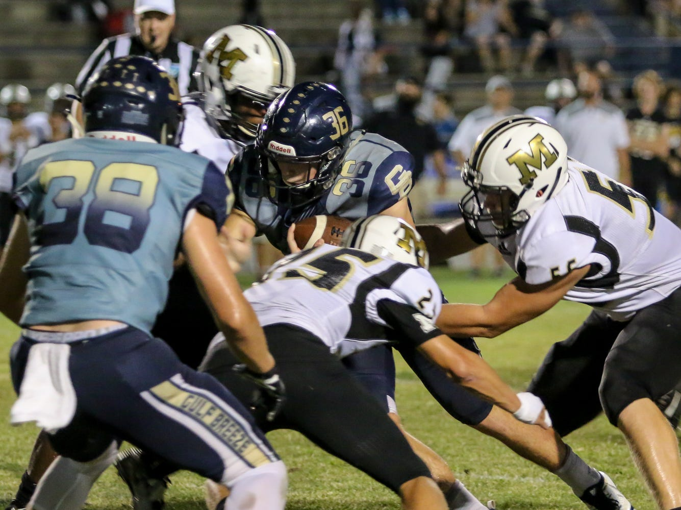Gulf Breeze running back Tyler Dittmer (36) gains positive yards after catching a last minute backwards toss from backup quarterback Cooper Harris, not pictured, against Milton in the District 2-6A game at Gulf Breeze High School on Friday.