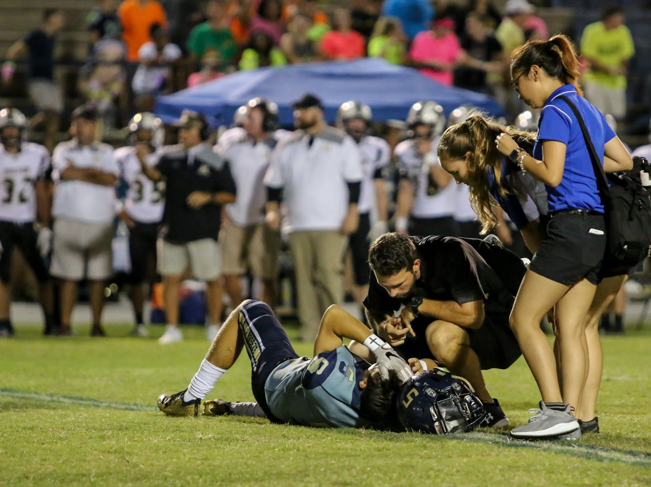 Trainers tend to Gulf Breeze starting quarterback Dylon Kelley (5) after he was injured on a play against Milton in the District 2-6A game at Gulf Breeze High School on Friday.