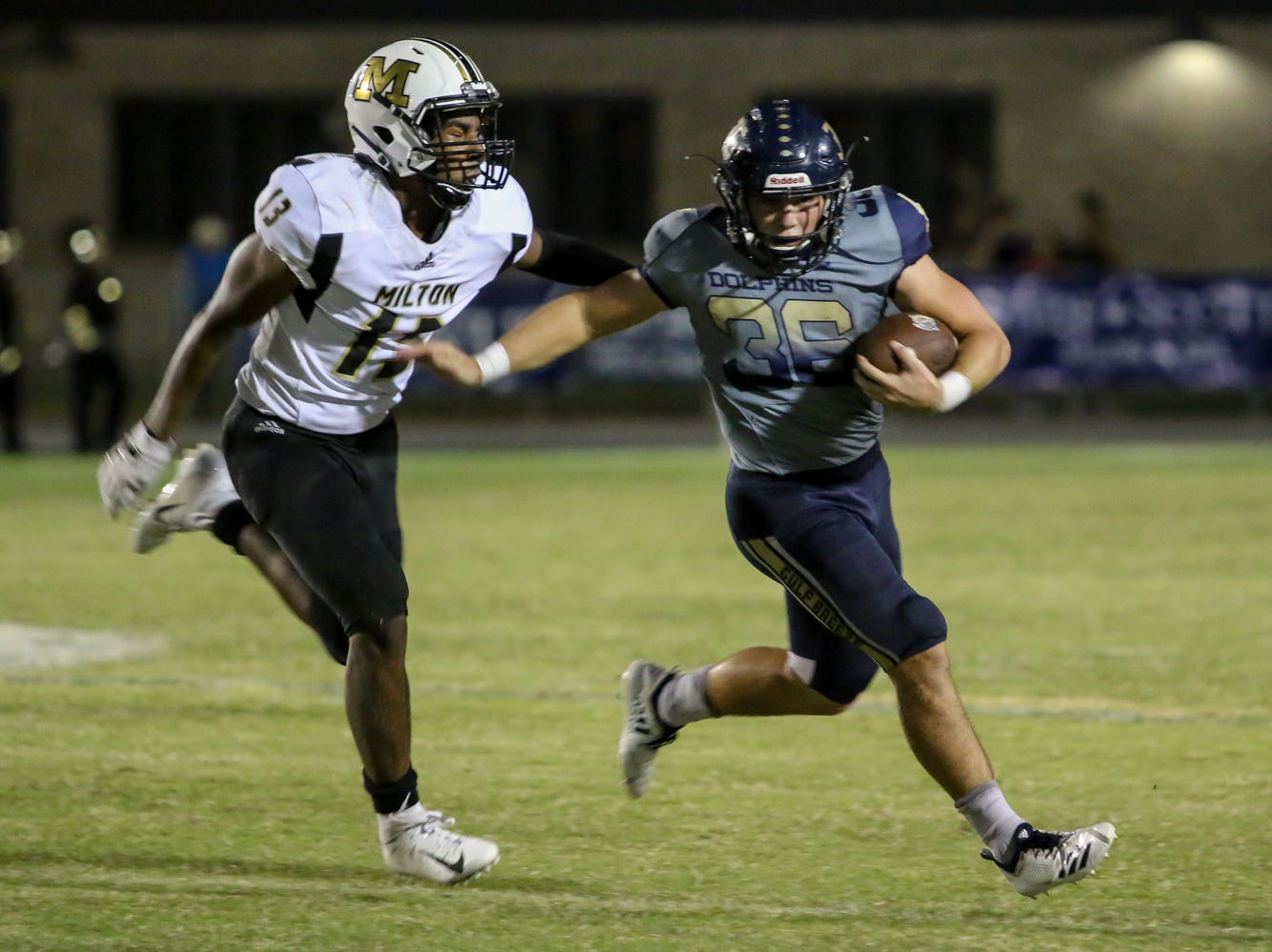 Gulf Breeze's Tyler Dittmer (36) stiff arms and gets away from Milton's Kameryn Hall in the District 2-6A game at Gulf Breeze High School on Friday, September 28, 2018.