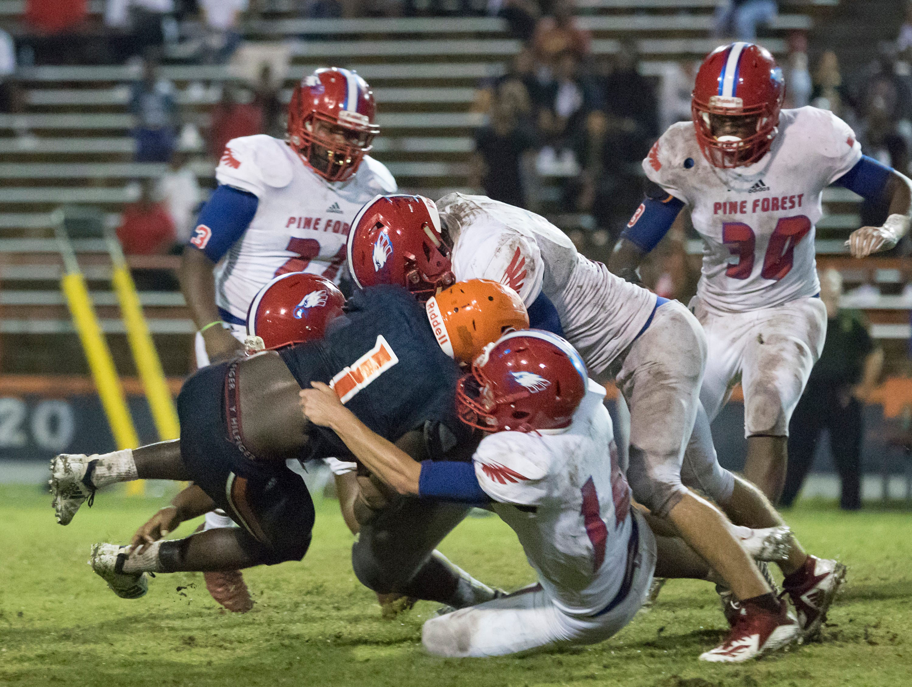 A host of Eagles take down Frank Peasent (1) as the Gators turn over the ball on downs during the Pine Forest vs Escambia football game at Escambia High School in Pensacola on Friday, September 28, 2018.