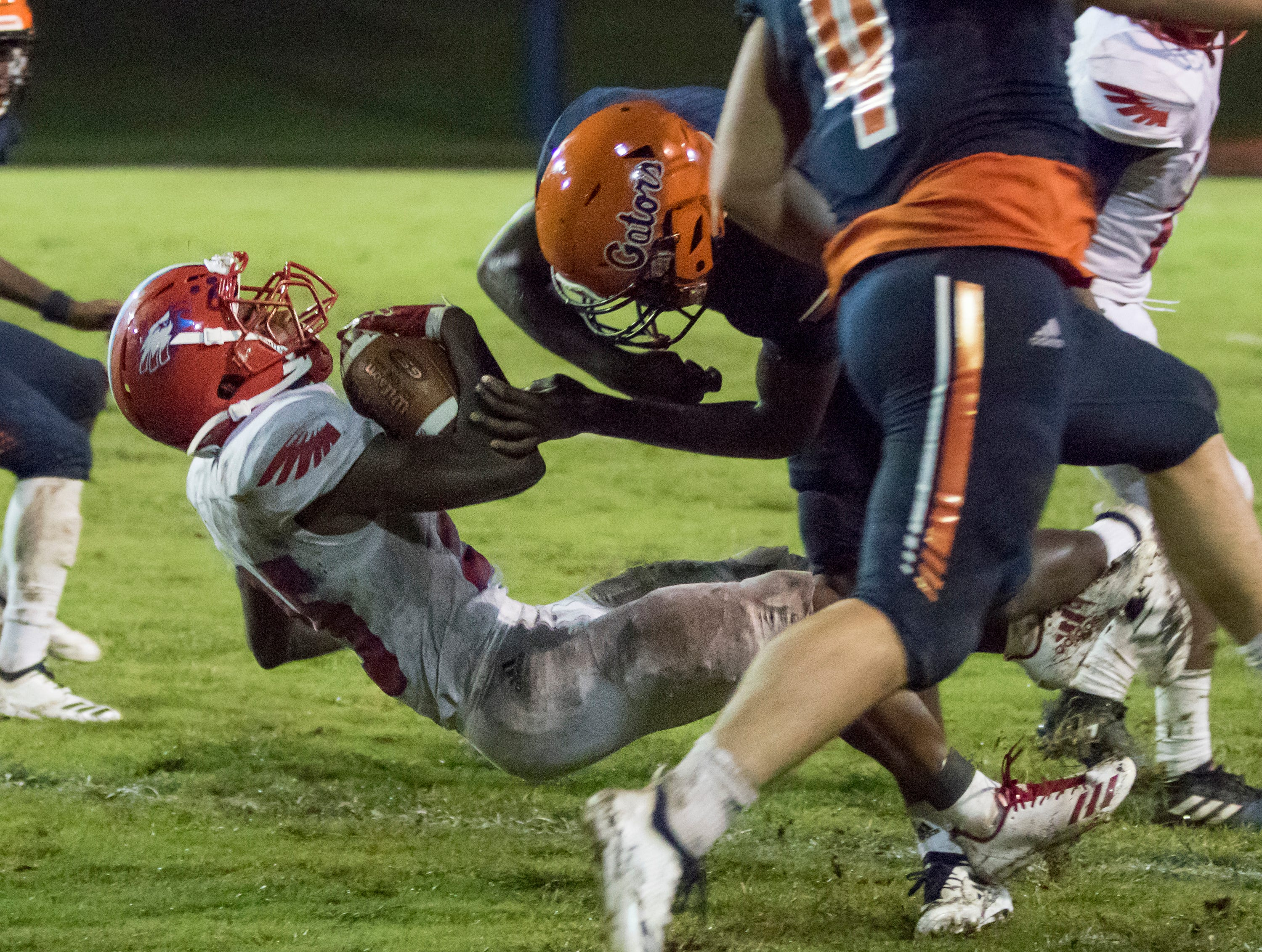 Jesse Saulsberry (12) puts a stop to a long run by Anwar Lewis (25) with a big hit during the Pine Forest vs Escambia football game at Escambia High School in Pensacola on Friday, September 28, 2018.
