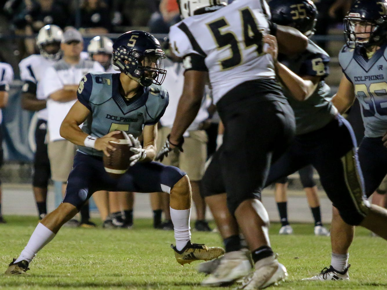 Gulf Breeze quarterback Dylon Kelley (5) keeps the ball and runs in for a touchdwon in the District 2-6A game against Milton at Gulf Breeze High School on Friday.