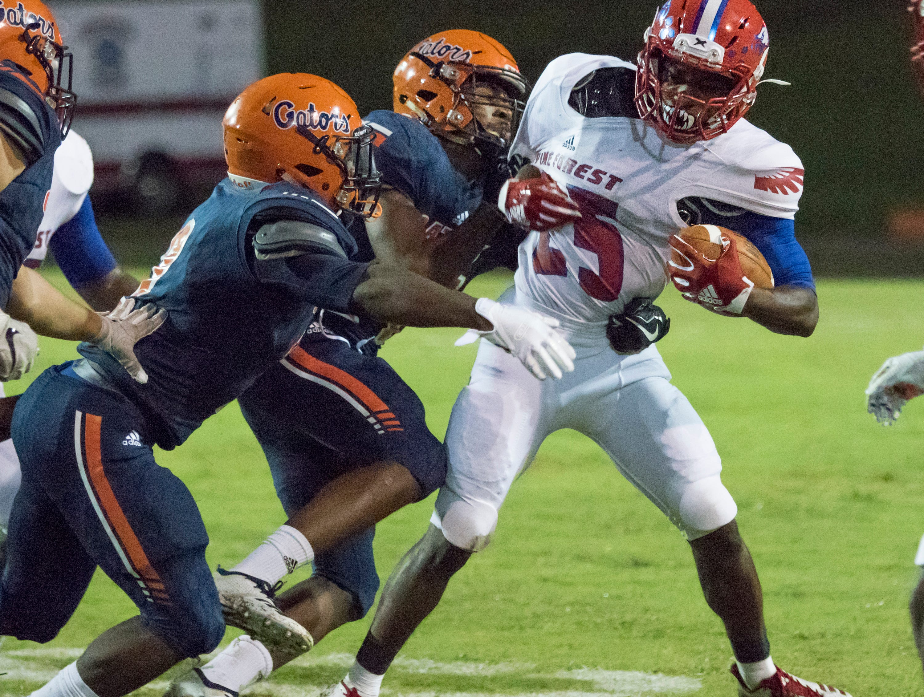 Anwar Lewis (25) gets wrapped up during the Pine Forest vs Escambia football game at Escambia High School in Pensacola on Friday, September 28, 2018.