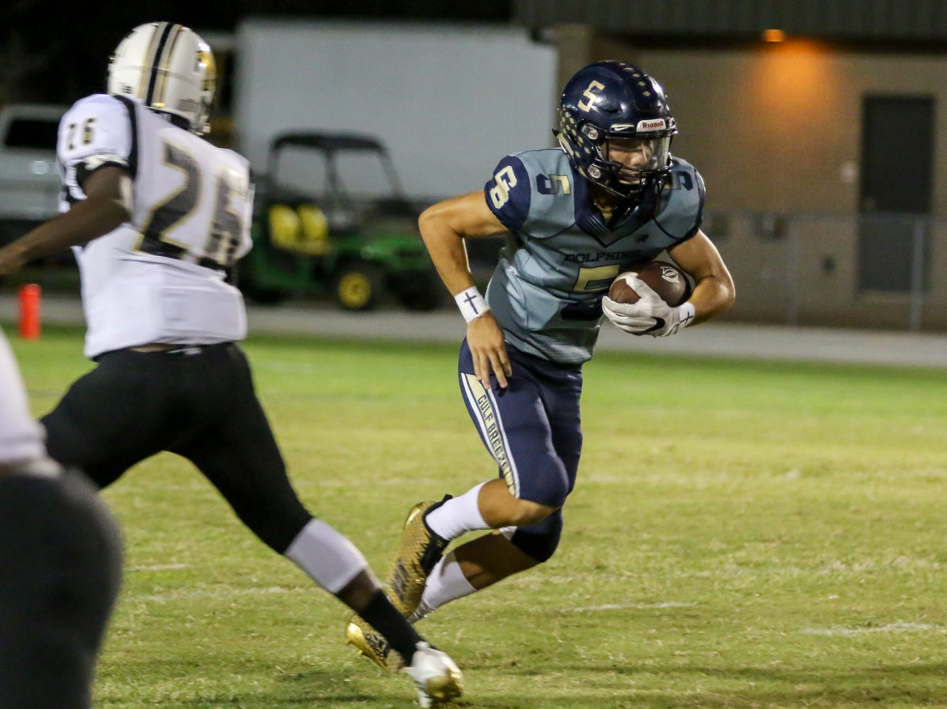 Gulf Breeze quarterback Dylon Kelley (5) keeps the ball and jukes left against Milton's Isaiah Rushing (26) in the District 2-6A game at Gulf Breeze High School on Friday.