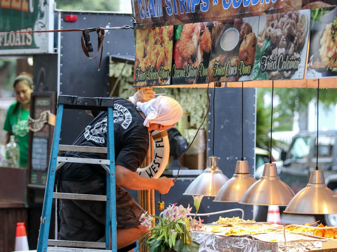 A worker puts the finishing touches on a food stand on the first day of the 41st annual Pensacola Seafood Festival in downtown Pensacola on Friday, September 28, 2018. The festival, which features multiple food vendors, artists, cooking demonstrations, live music and more, is free to enter and continues through Sunday.