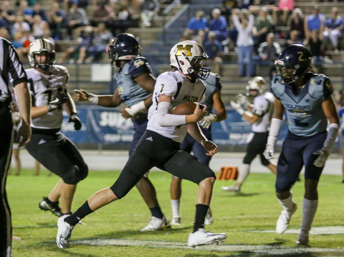 Milton quarterback Tyler Buchanan (7) rushes in for a touchdown against the Dolphins in the District 2-6A game at Gulf Breeze High School on Friday.
