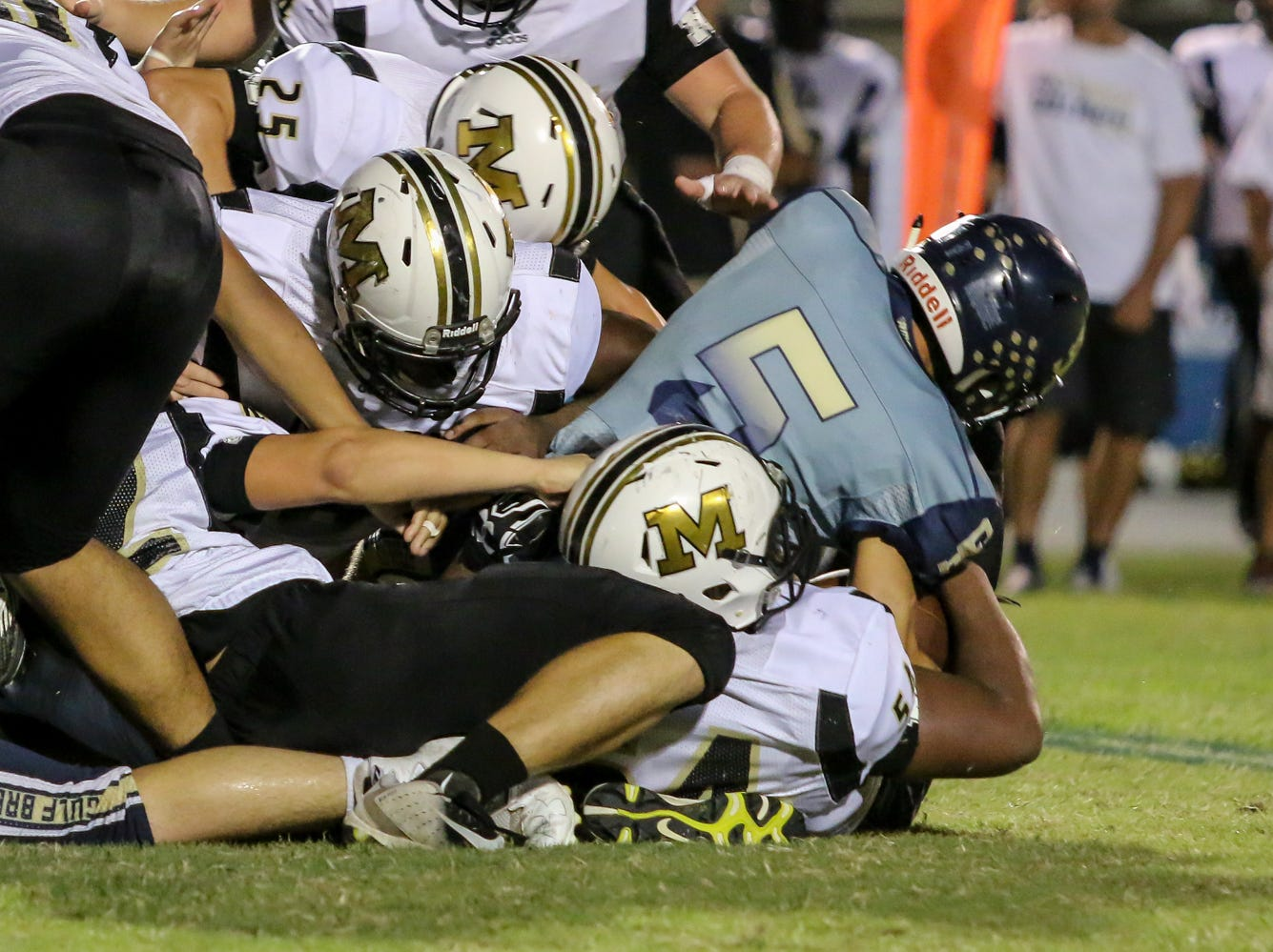 Gulf Breeze starting quarterback Dylon Kelley (5) gets injured on this play against Milton after being twisted up on the tackle in the District 2-6A game at Gulf Breeze High School on Friday.
