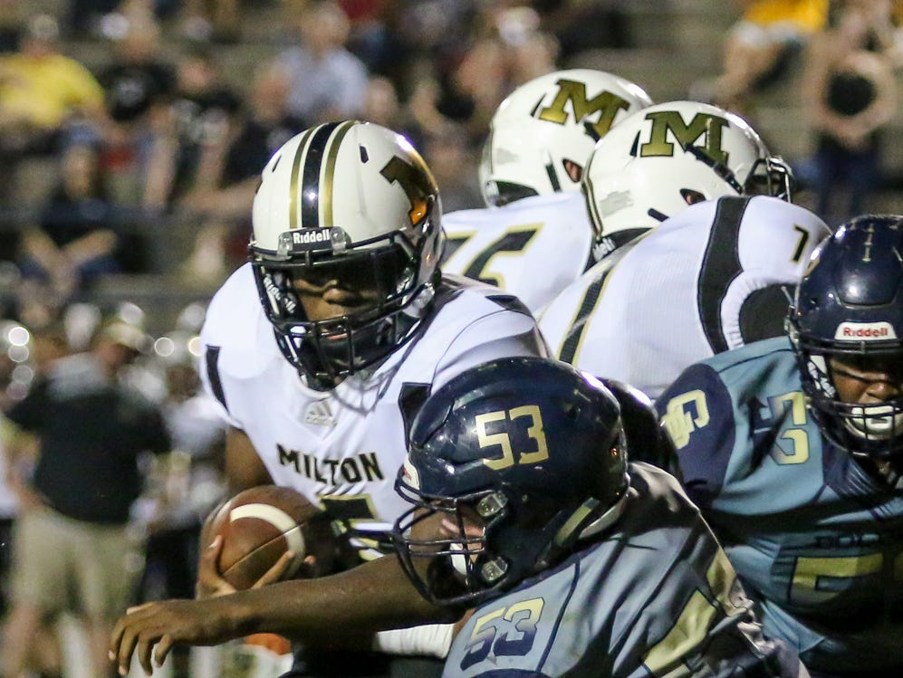 Milton's Tobias Daniels (5) tries to push his way past Gulf Breeze's Owen Herrick (53) in the District 2-6A game at Gulf Breeze High School on Friday.
