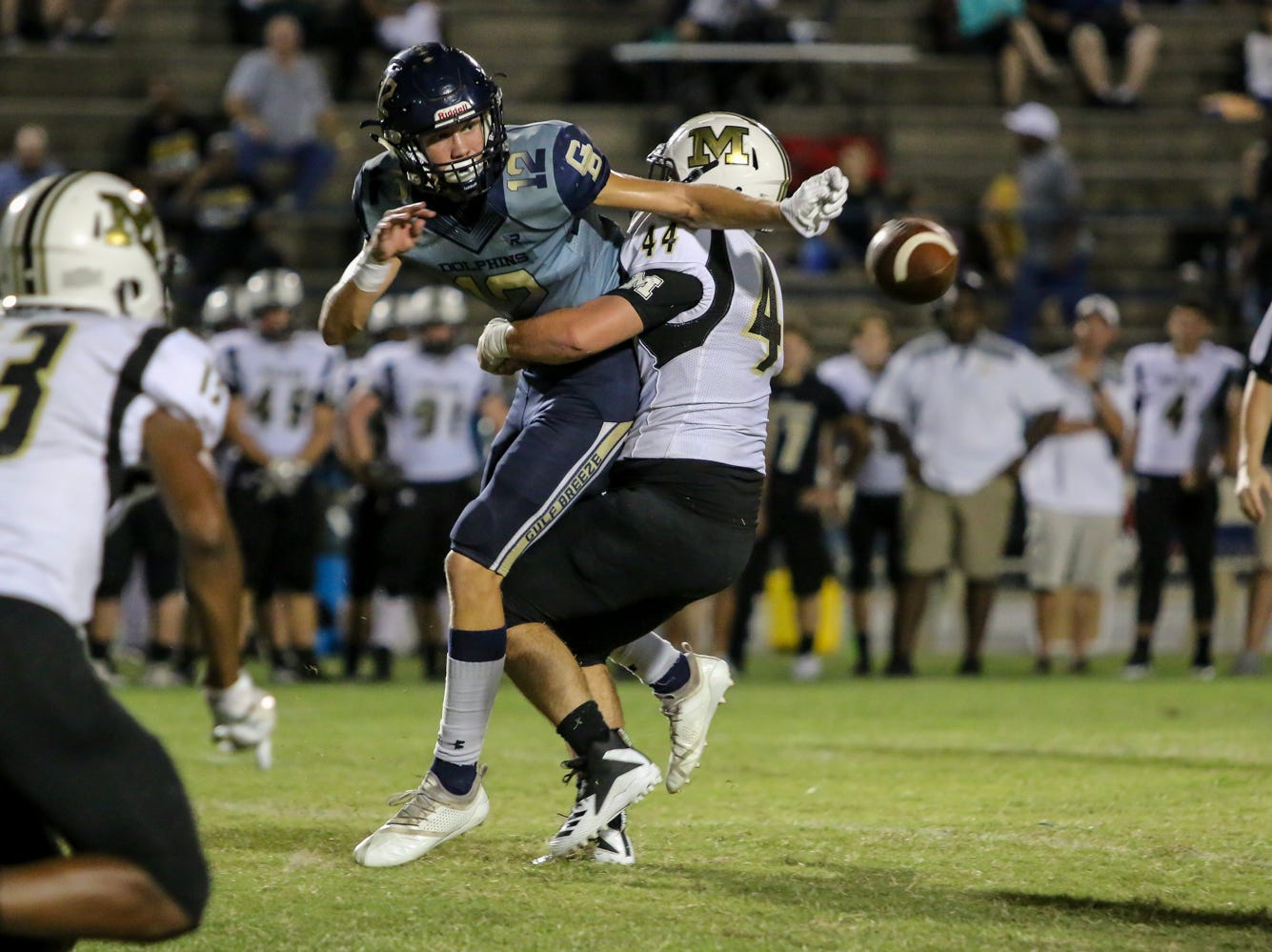On the first play after starting quarterback Dylon Kelley was injured and left the game, Gulf Breeze's Cooper Harris (12) makes an impressive backwards toss to running back Tyler Dittmer, not pictured, to avoid a sack by Milton's Trevor Lunsford (44) at Gulf Breeze High School on Friday, September 28, 2018.