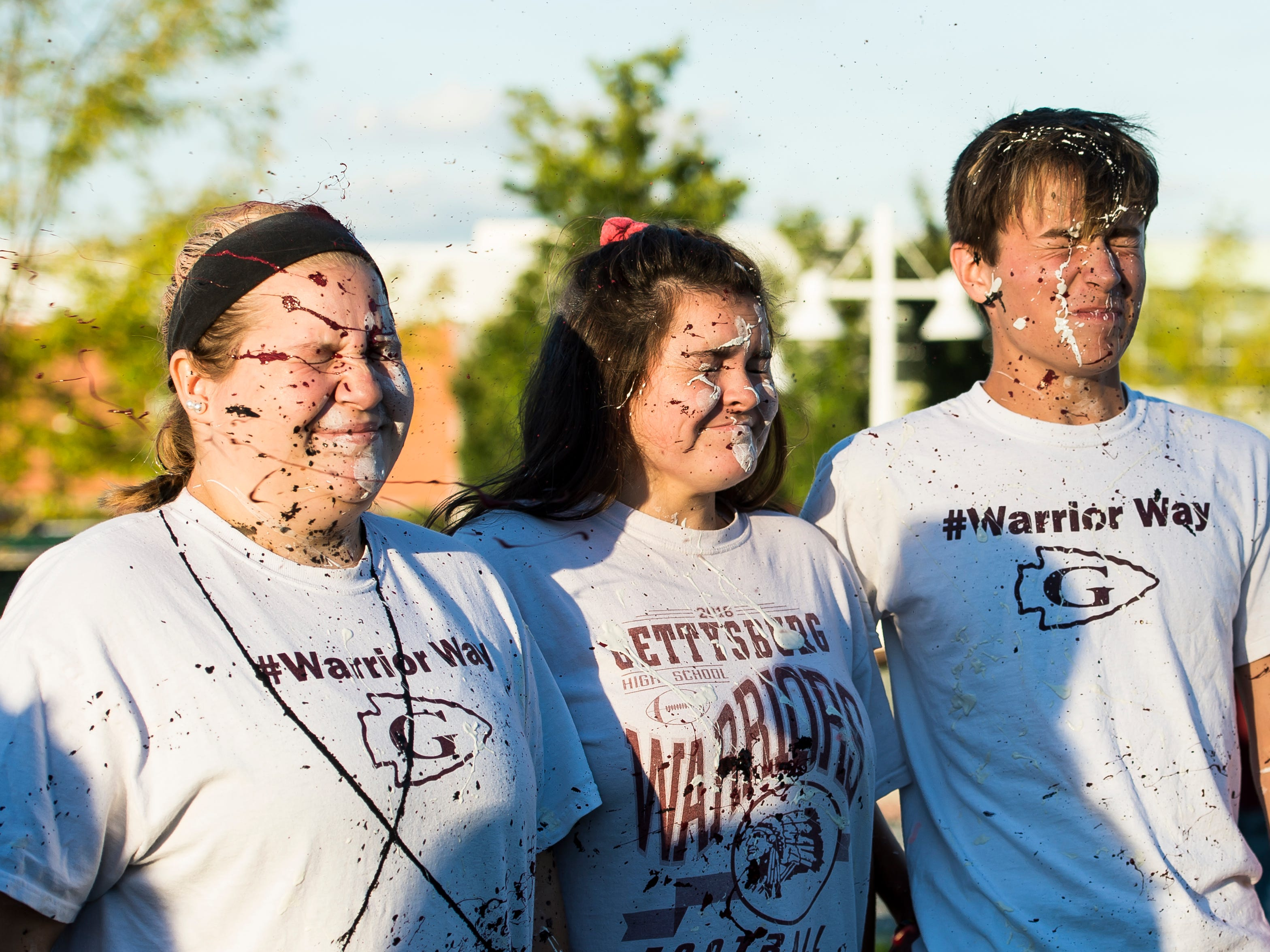"""(From left) Gettysburg High School students Maddie Welty, Faith Miley and Brett Keller get hit with paint during a """"splatter-fest"""" prior to the football game against Eastern York on Friday, September 28, 2018. The fest helped raise money for the school's Mini-THON."""