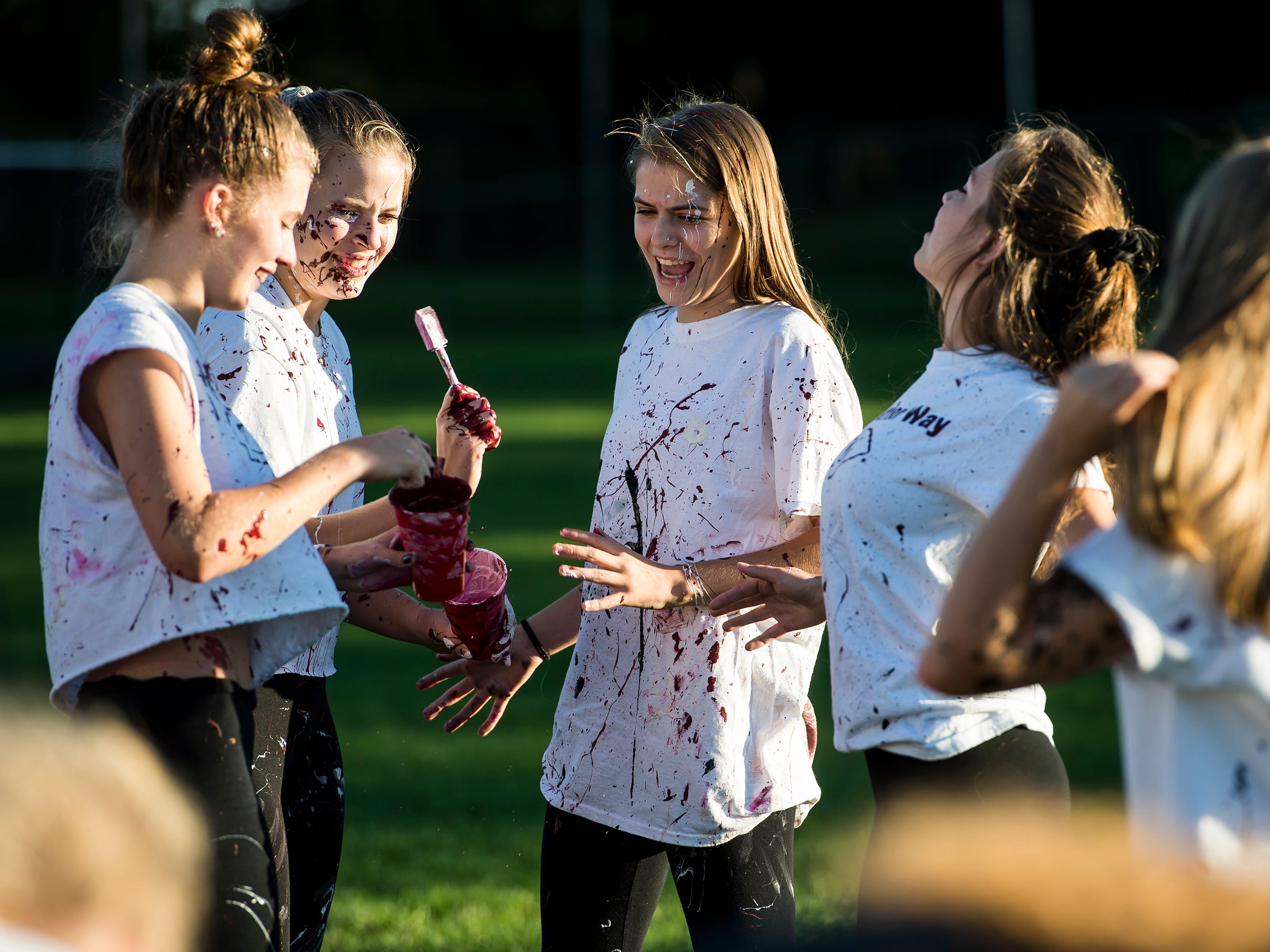 """Gettysburg Area High School students cover each other in paint during a """"splatter-fest"""" prior to the football game against Eastern York on Friday, September 28, 2018. The fest helped raise money for the school's Mini-THON."""