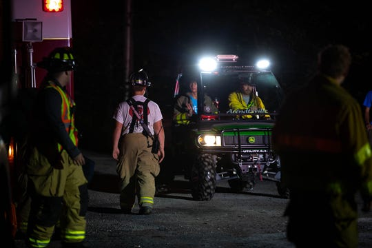 Firefighters drive an ATV as they pack up at the scene of a rescue, in which a man and a woman fell off a railroad bridge and into a ravine in the woods near the 1700 block of Chambersburg Road, Saturday, Sept. 29, 2018, in Franklin Township.