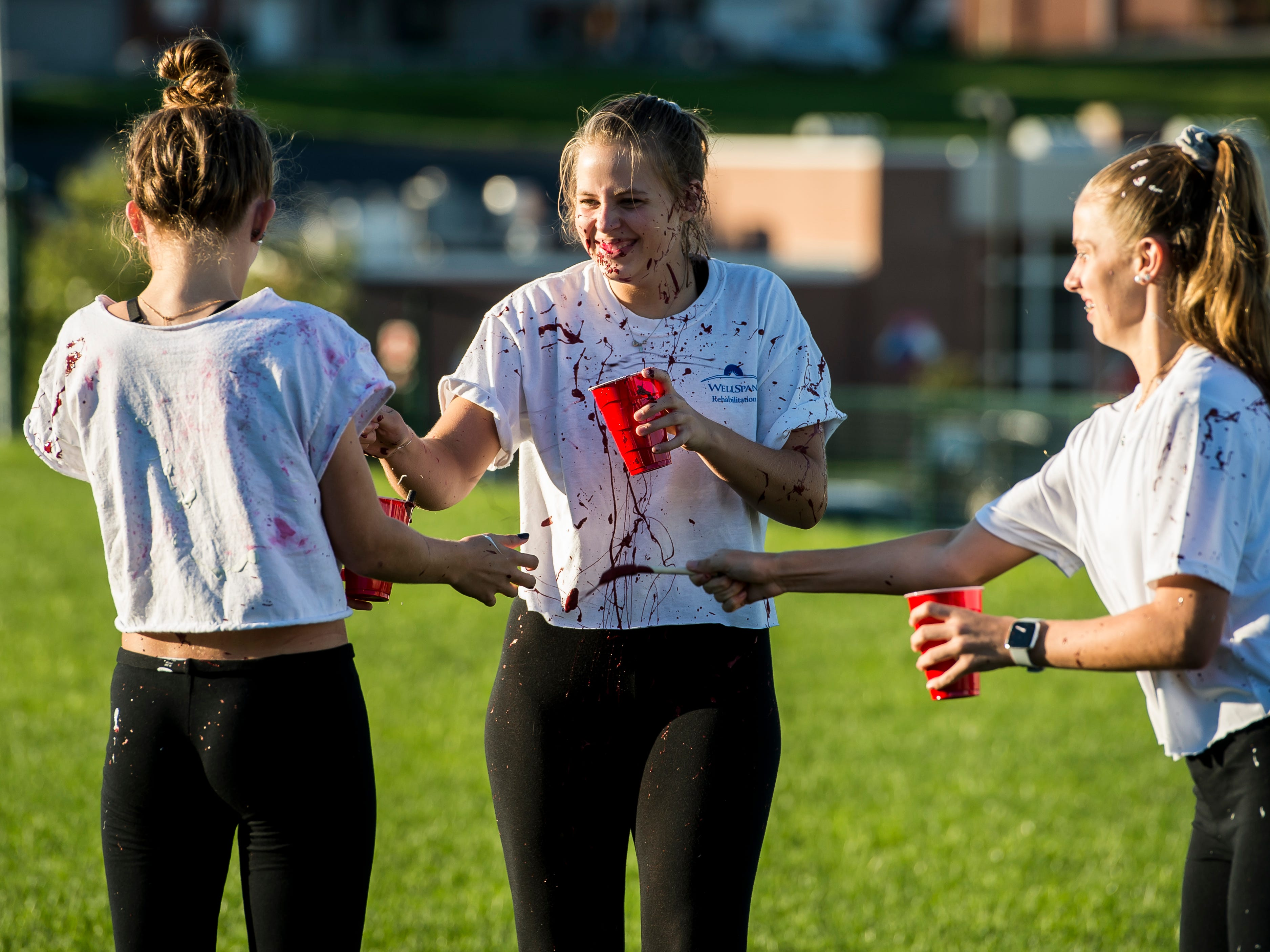 """Gettysburg High School students cover each other in paint during a """"splatter-fest"""" prior to the football game against Eastern York on Friday, September 28, 2018. The fest helped raise money for the school's Mini-THON."""