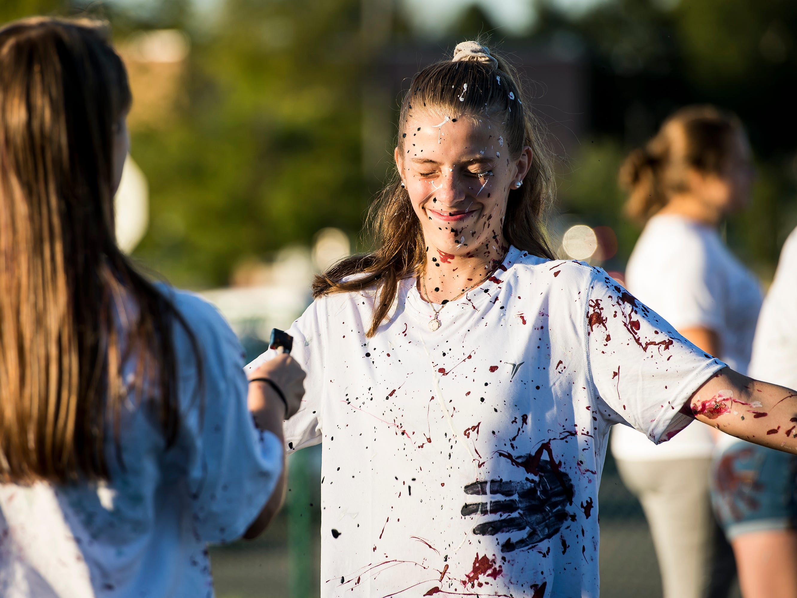 """A Gettysburg students gets covered in paint during a """"splatter-fest"""" prior to the football game against Eastern York on Friday, September 28, 2018. The fest helped raise money for the school's Mini-THON."""