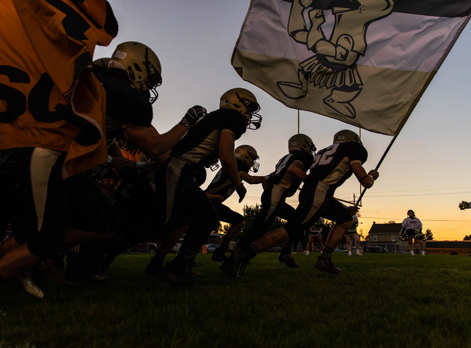 Delone's Andrew Shipley (52) carries the Delone Squires flag as he enters the field before a football game between Delone Catholic and Biglerville, Friday, Sept. 28, 2018, in McSherrystown. Delone led Biglerville 35-0 at the half.