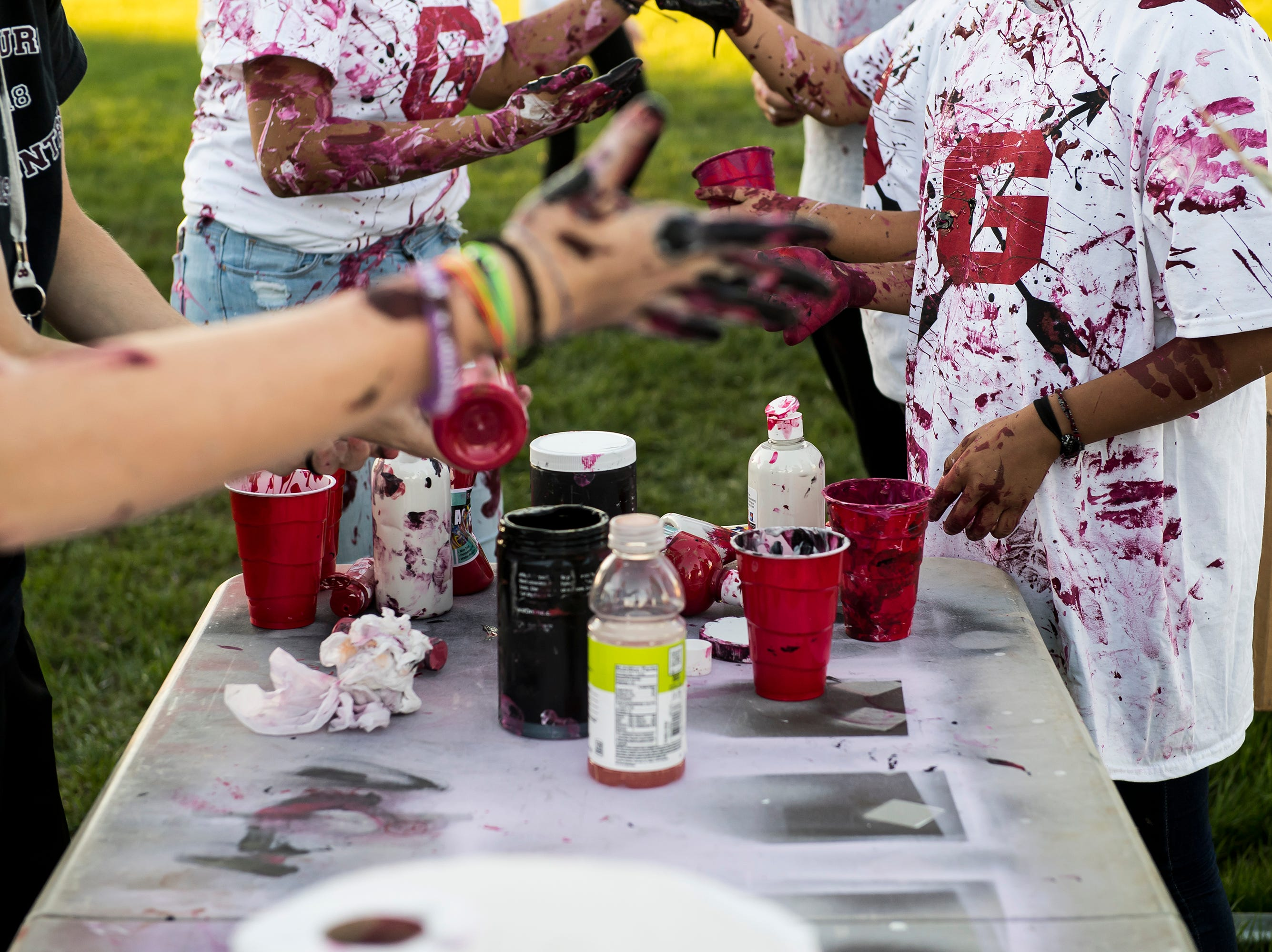"""Gettysburg students at the paint table during a """"splatter-fest"""" prior to the football game against Eastern York on Friday, September 28, 2018. The fest helped raise money for the school's Mini-THON."""